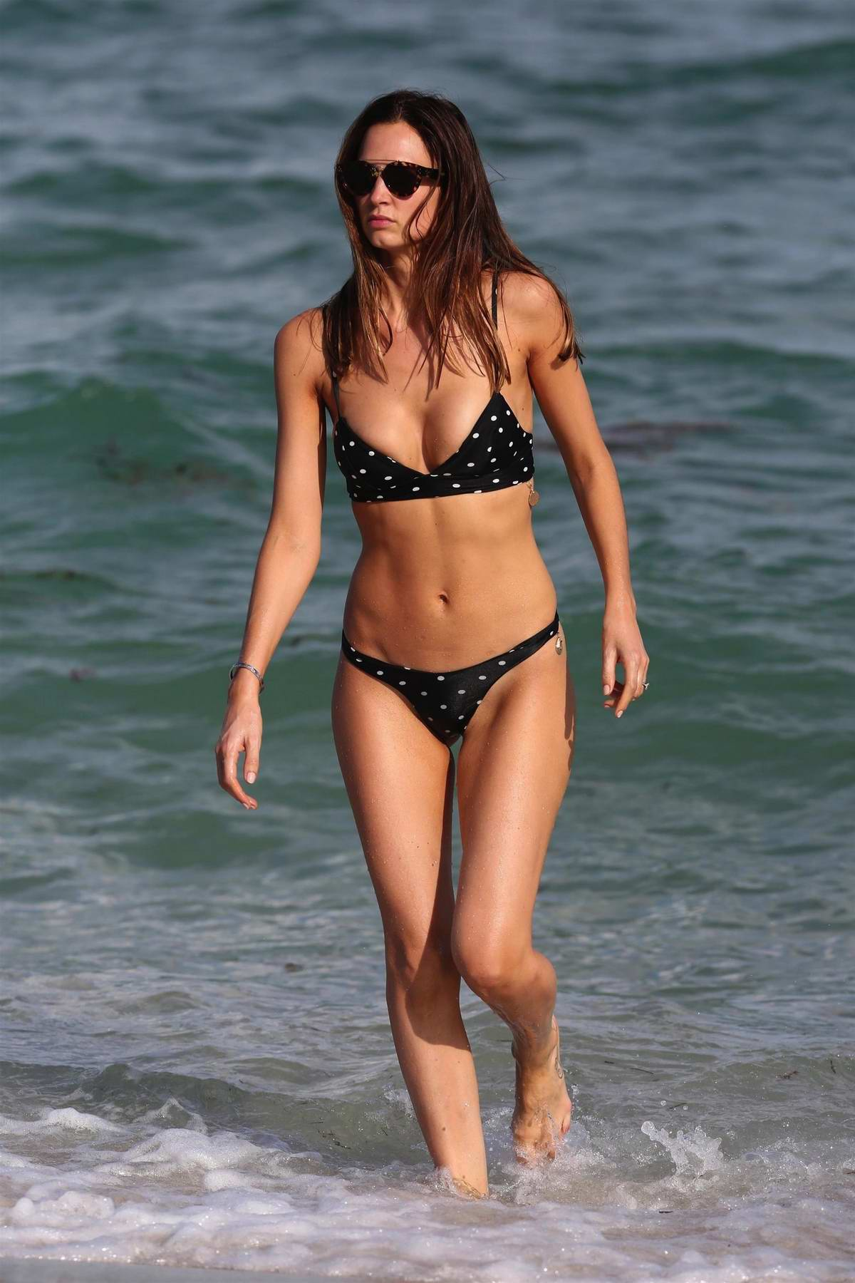 Alice Amelie in a black polka dotted bikini enjoys the beach in Miami, Florida