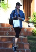 Chrissy Teigen sports a hat and shows off a ripped denim jacket as she leaves a friends house in Los Angeles