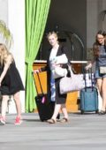 Dakota and Elle Fanning cart their luggage as they leave a hotel in Los Angeles