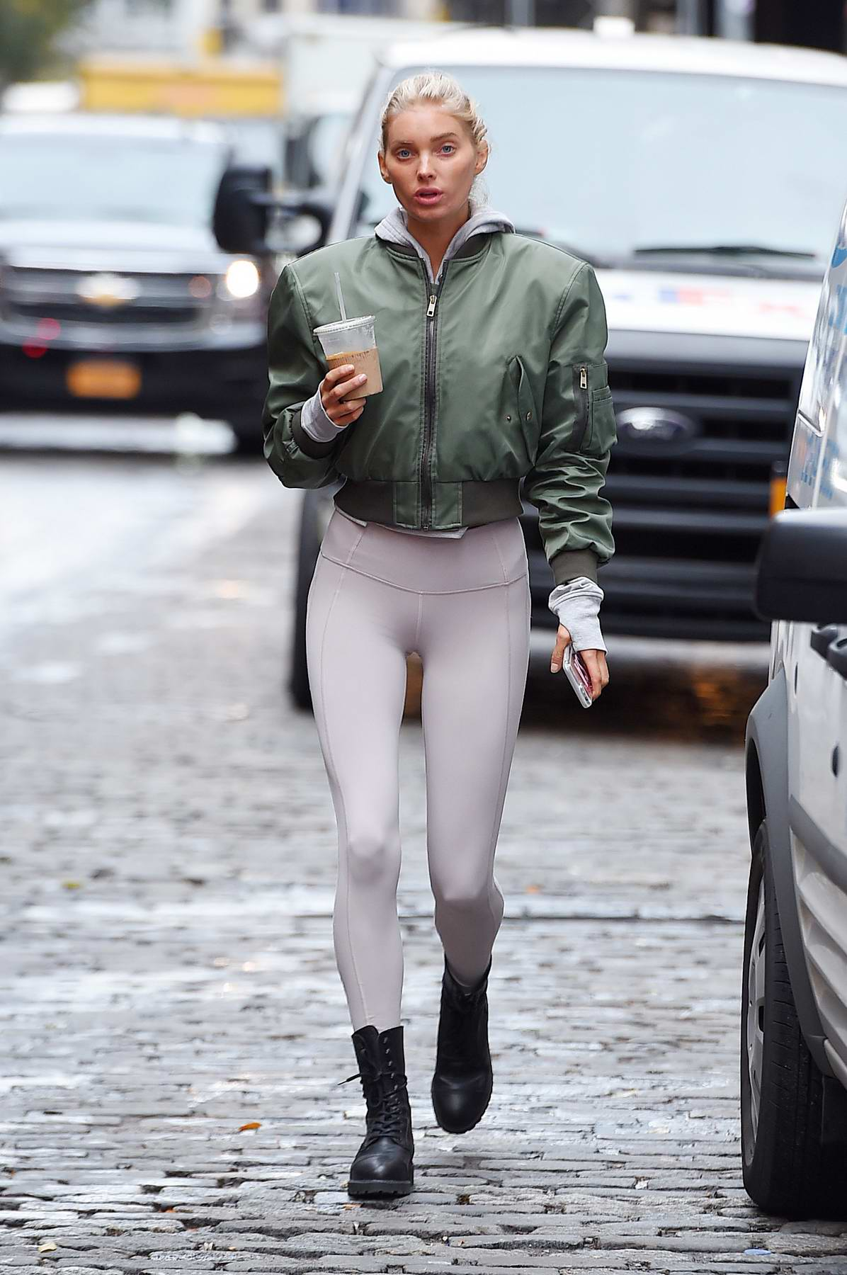 Elsa Hosk in a green jacket and white leggings out and about in SoHo, New York City