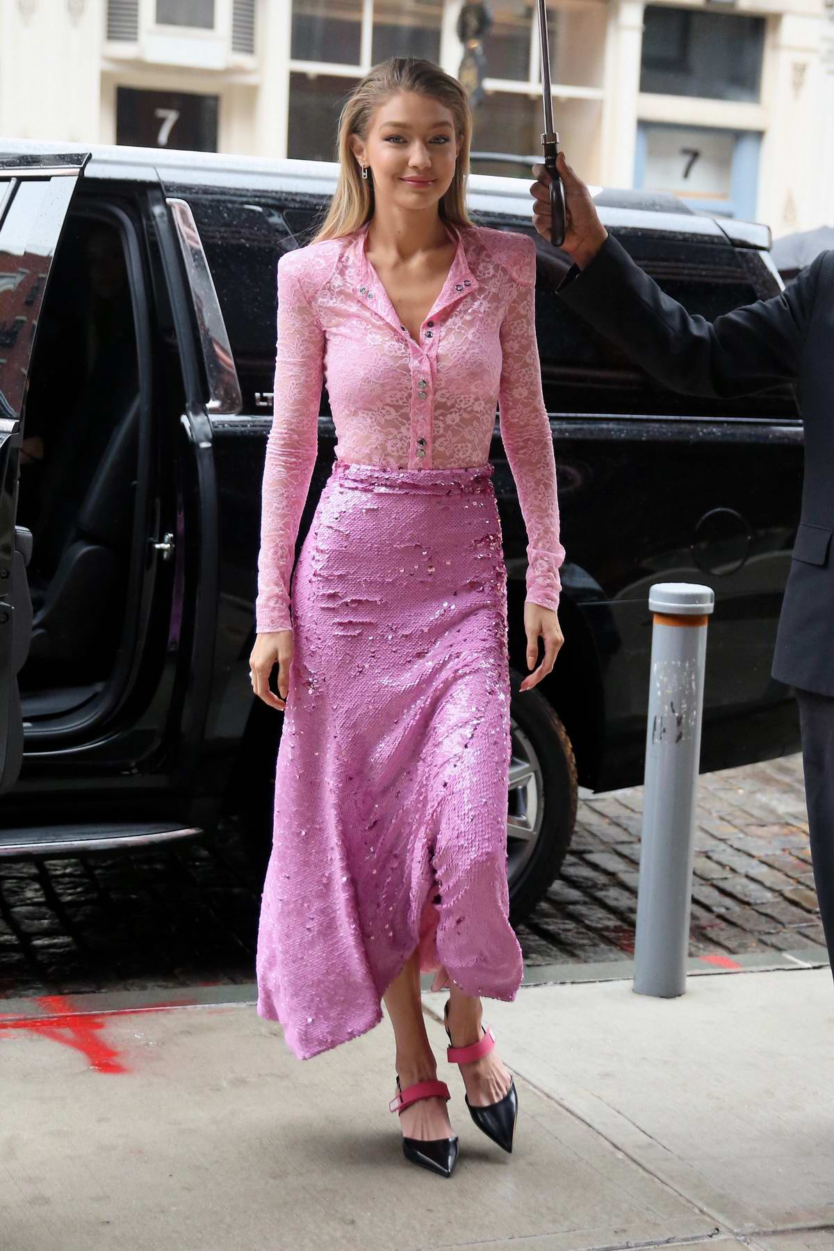 Gigi Hadid wearing a pink outfit as she returns to her apartment in New York City