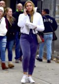 Iskra Lawrence dressed in a white jacket over a purple sweatsuit while out in New York City