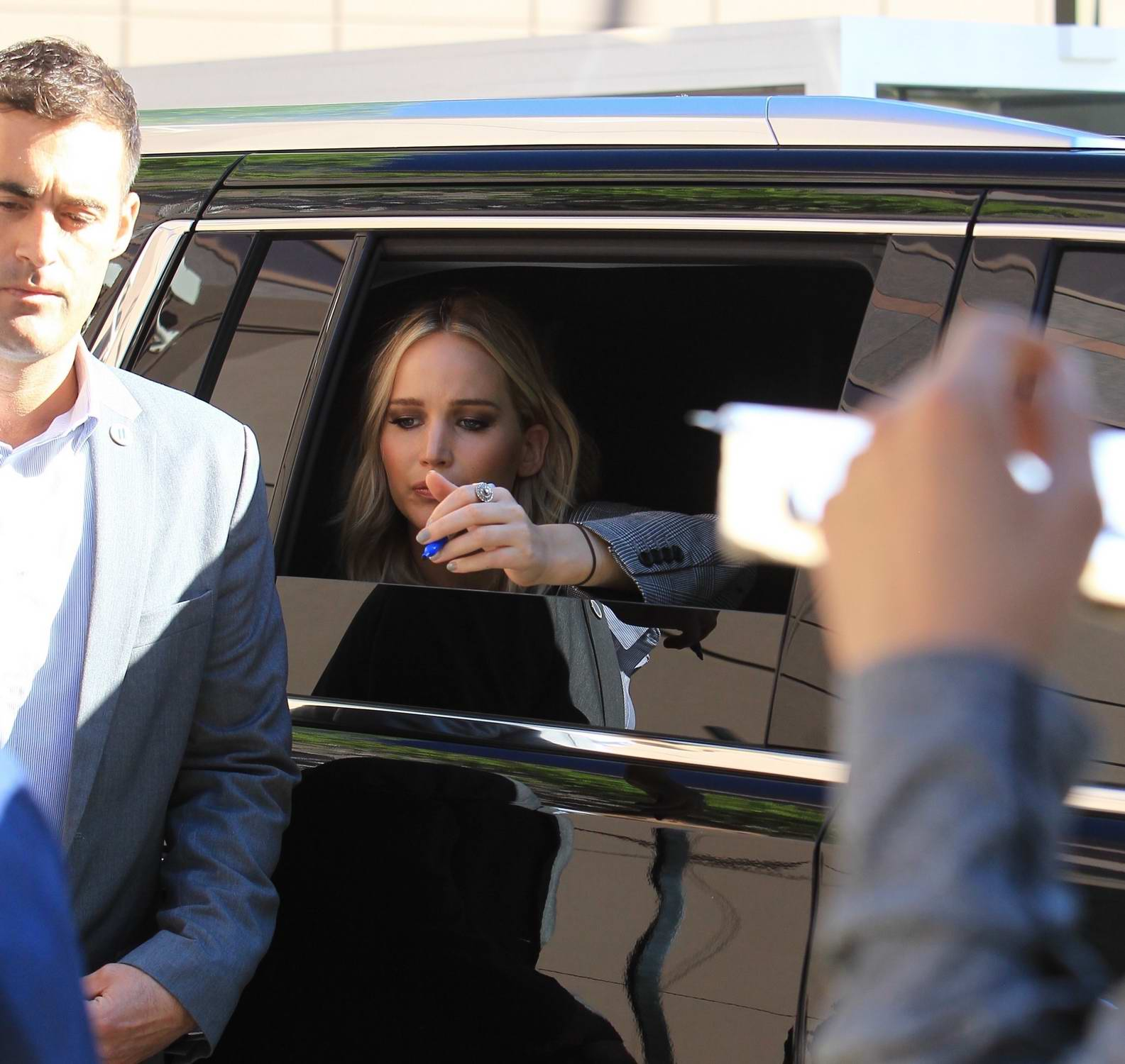 Jennifer Lawrence signs autographs for fans from her car at the Directors Guild of America in Hollywood, Los Angeles