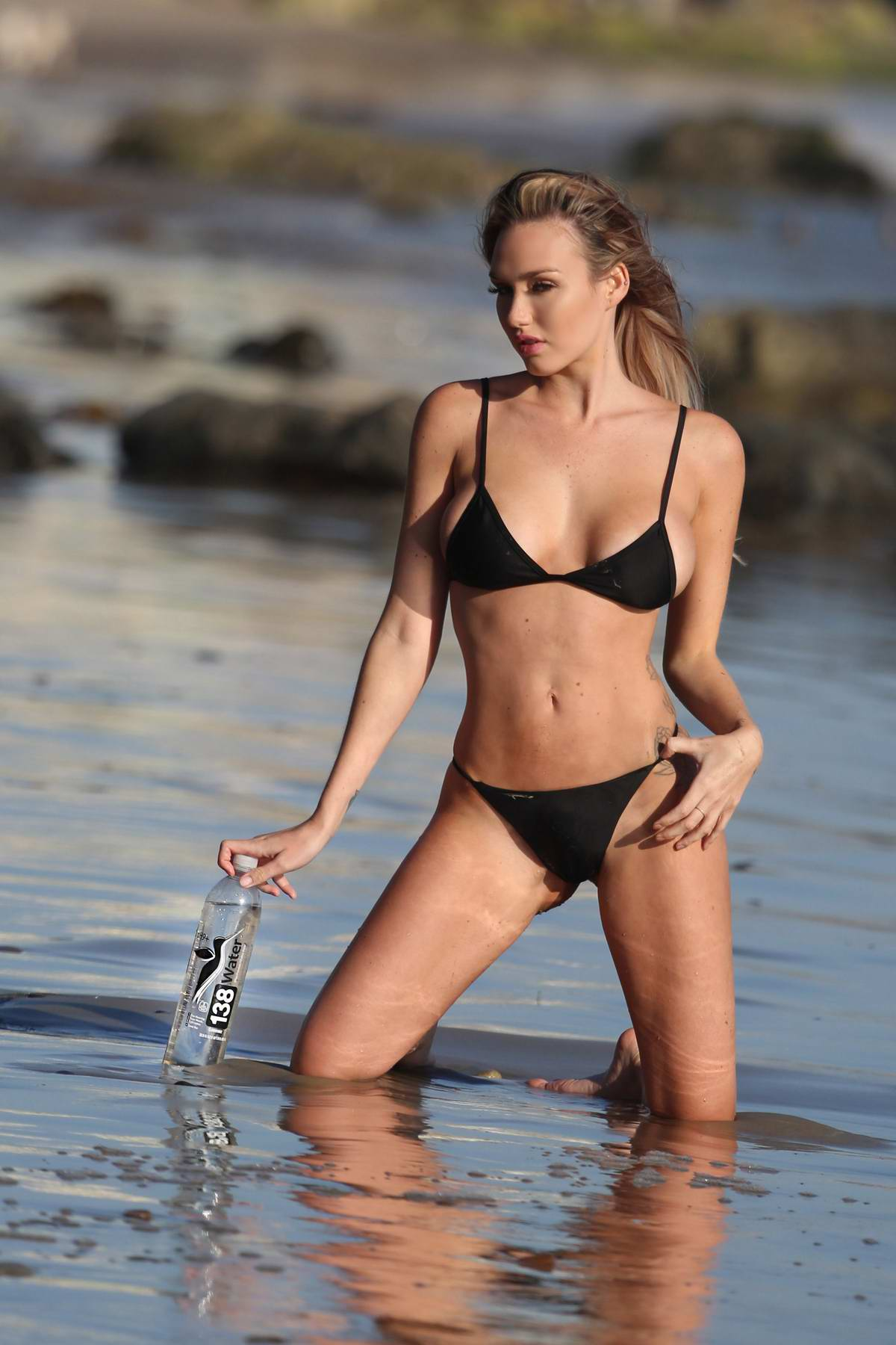 Jules Liesl wearing a black bikini on the set of a 138 Water photoshoot in Malibu, California