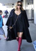 Katharine McPhee wears a black short dress paired with knee high red boots as she walks into LAX airport, Los Angeles