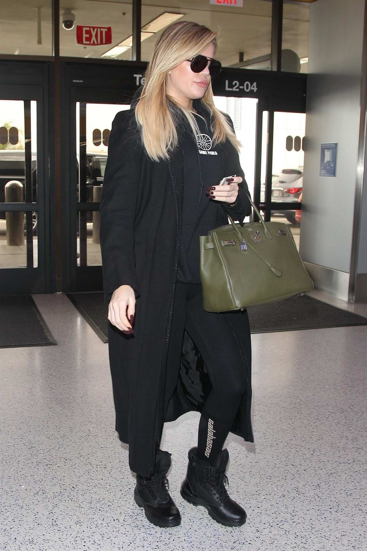 Khloe Kardashian spotted amidst pregnancy rumors while departing on a flight at LAX Airport, Los Angeles