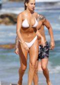 Madi Edwards wears a white bikini on a beach outing with her boyfriend in Sydney, Australia