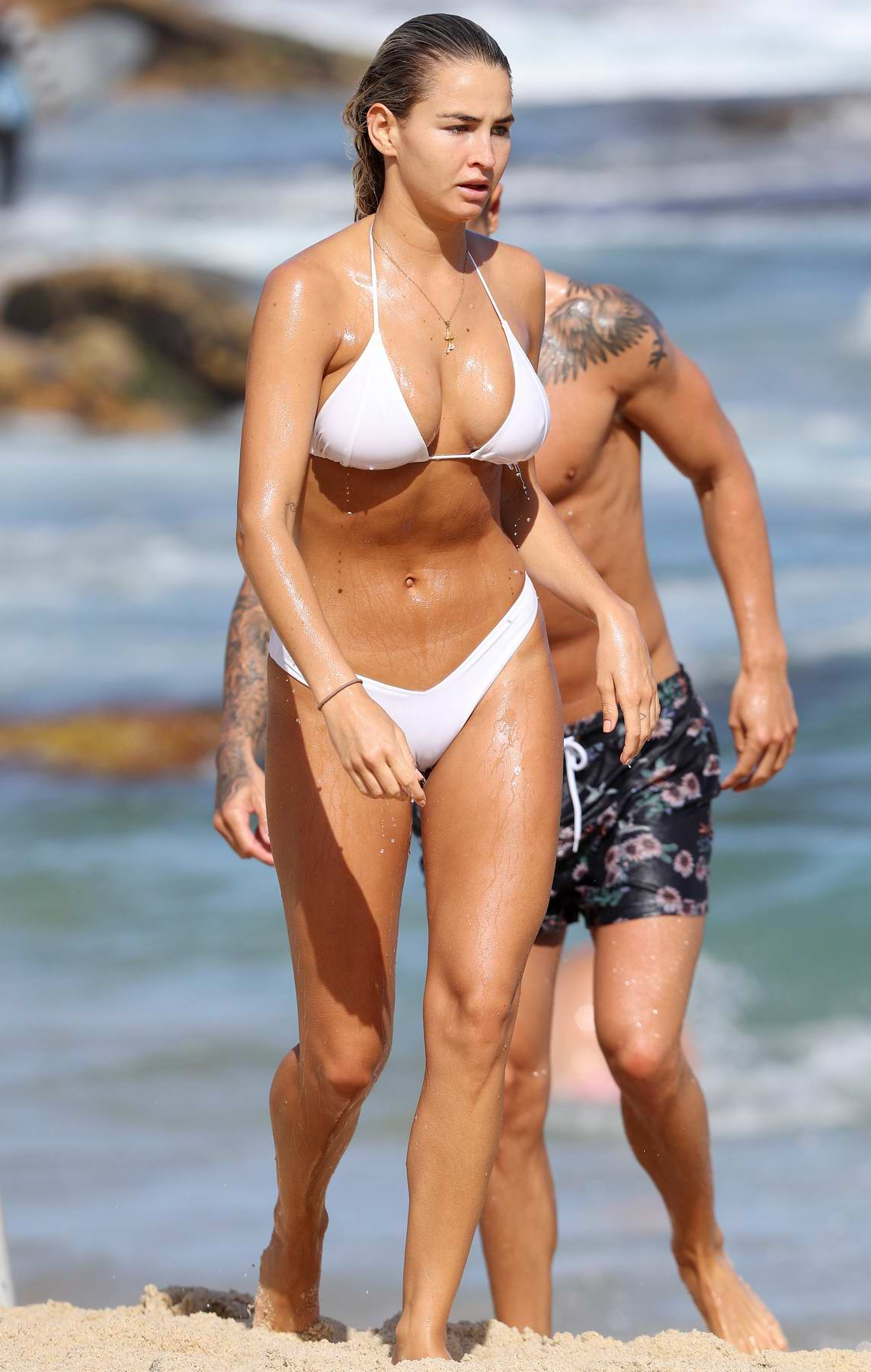 Madi Edwards wears a white bikini on a beach outing with her boyfriend in Sydney, Australia
