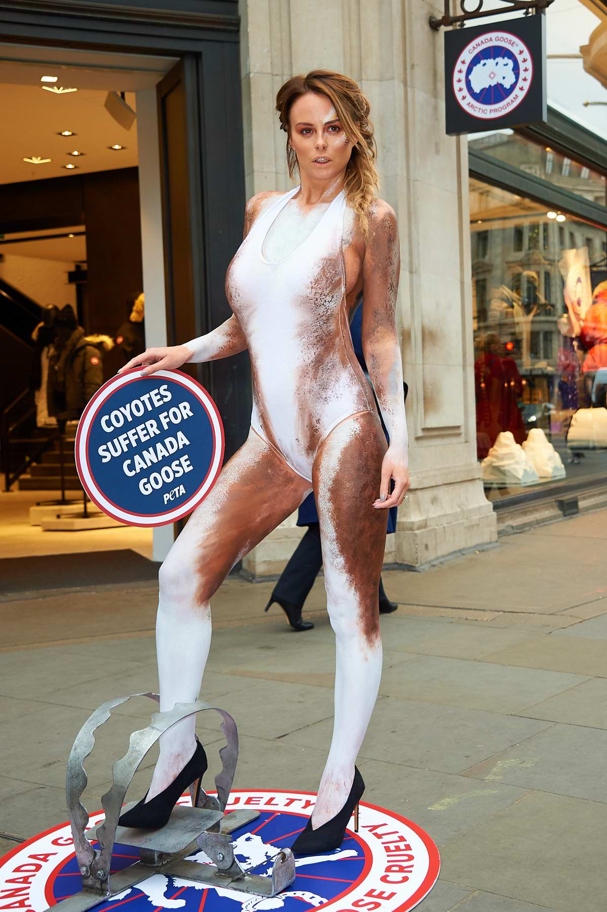 Rhian Sugden with her body painted as a coyote protests outside Canada Goose in Regent Street, London