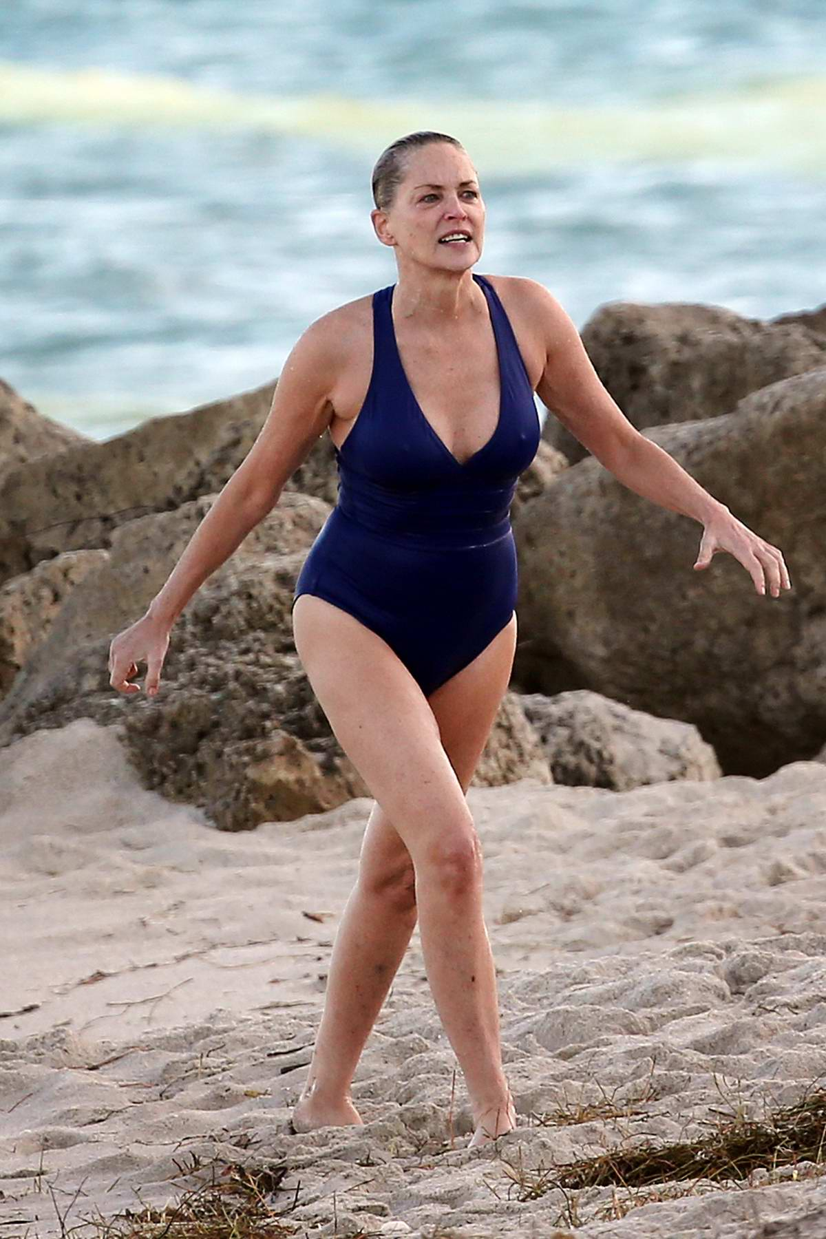 Sharon Stone in a blue swimsuit enjoying the beach in Miami, Florida