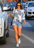 Alessandra Ambrosio wearing a trendy grey and white sweater paired with denim shorts while out grabbing a salad bowl in Los Angeles