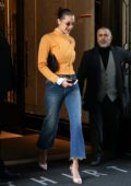 Bella Hadid wearing a yellow leather jacket and jeans as she leaves her apartment in New York City
