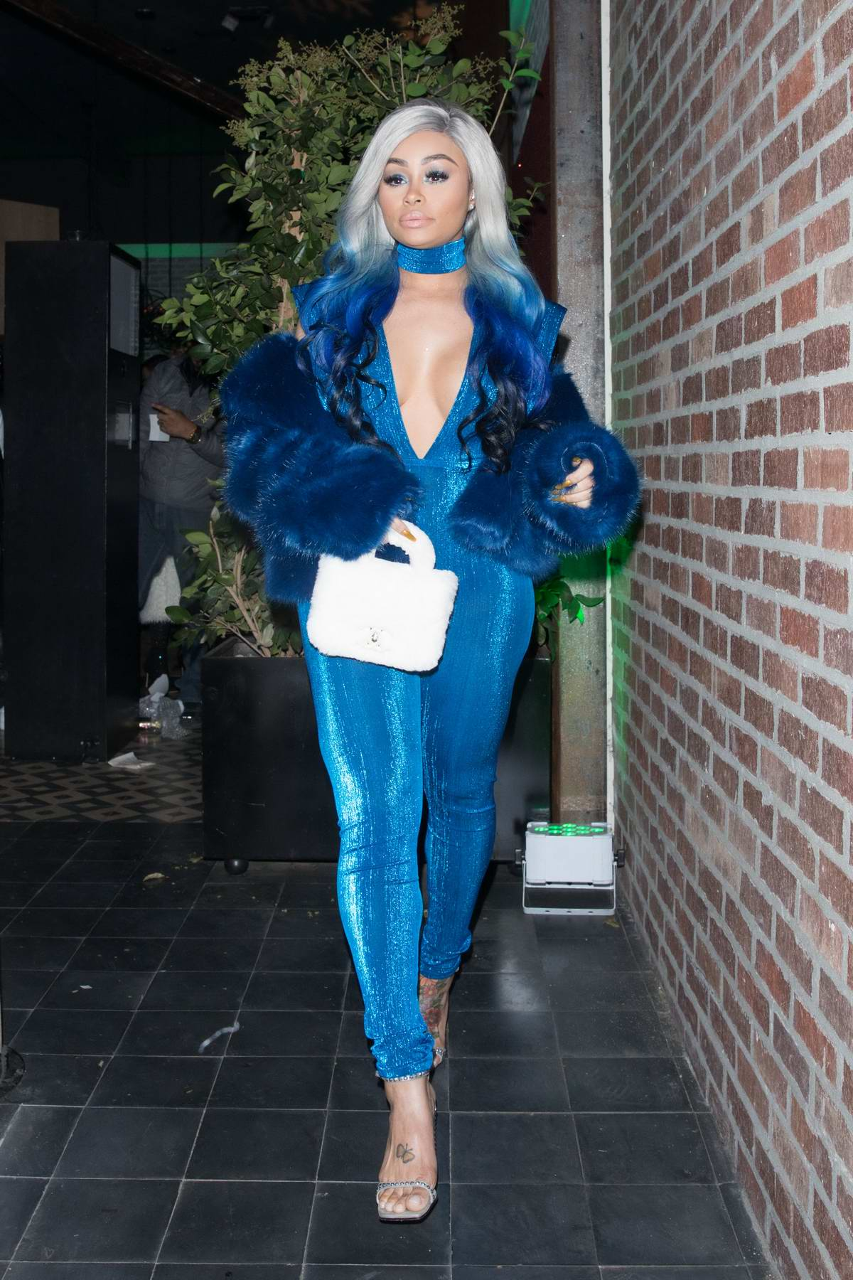 Blac Chyna wearing electric blue outfit to match her hair while at Karrueche Tran's holiday party at the Paloma in West Hollywood, Los Angeles