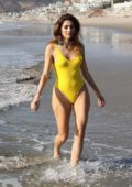Blanca Blanco stands out in a bright yellow swimsuit as she strolls the beaches of Malibu, California