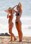 Candice Swanepoel flaunts her growing baby bump in a black bikini while enjoying the beach in Brazil