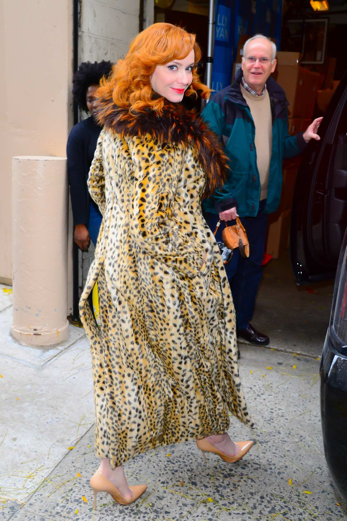 16ecdd419fb8 christina hendricks wearing a fur lapel leopard print coat as she arrives  at an office building in new york city-131217_6