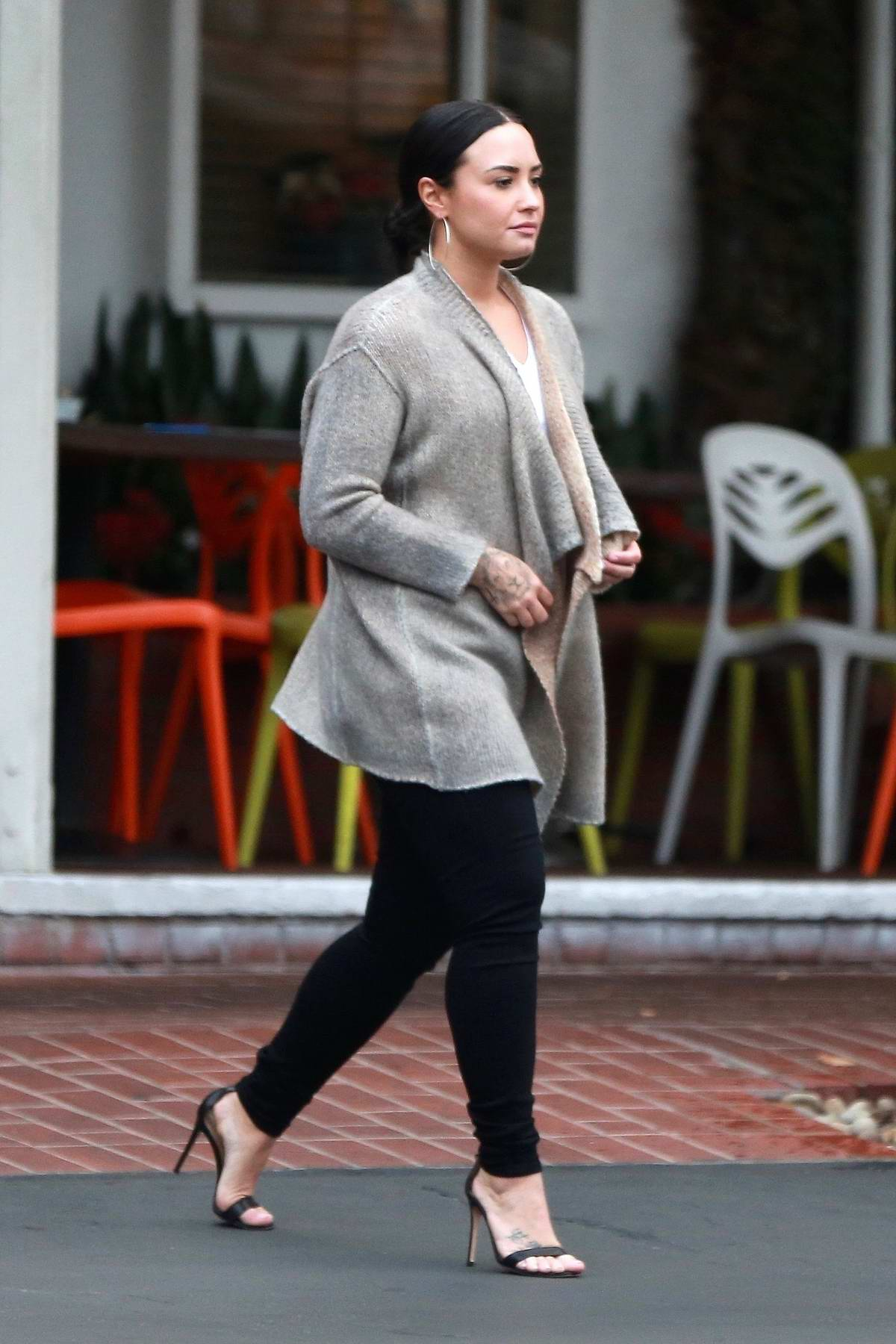 Demi Lovato spotted leaving Fred Segal wearing a cardigan and black skinny jeans, West Hollywood, Los Angeles