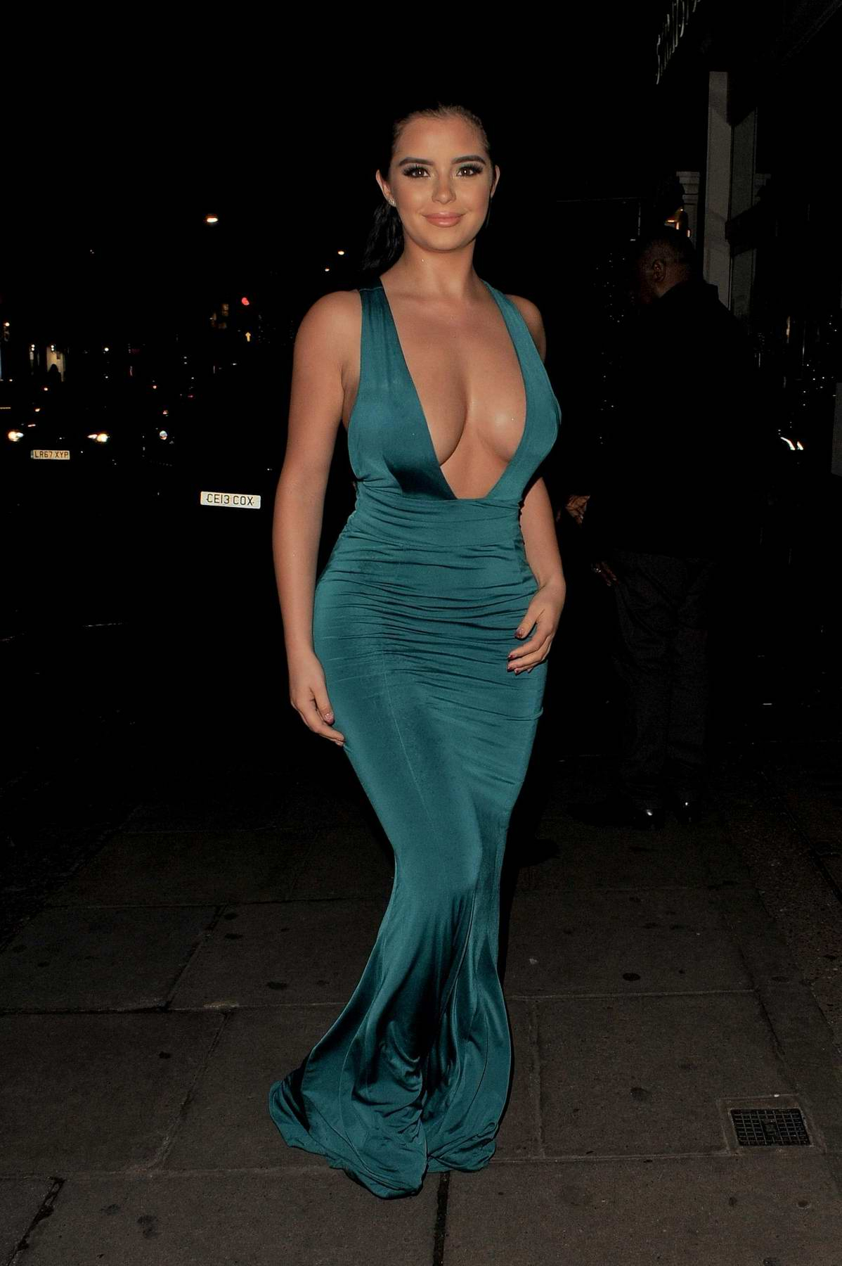 Demi Rose Mawby wearing a teal deep cut dress while on a night out in Mayfair, London