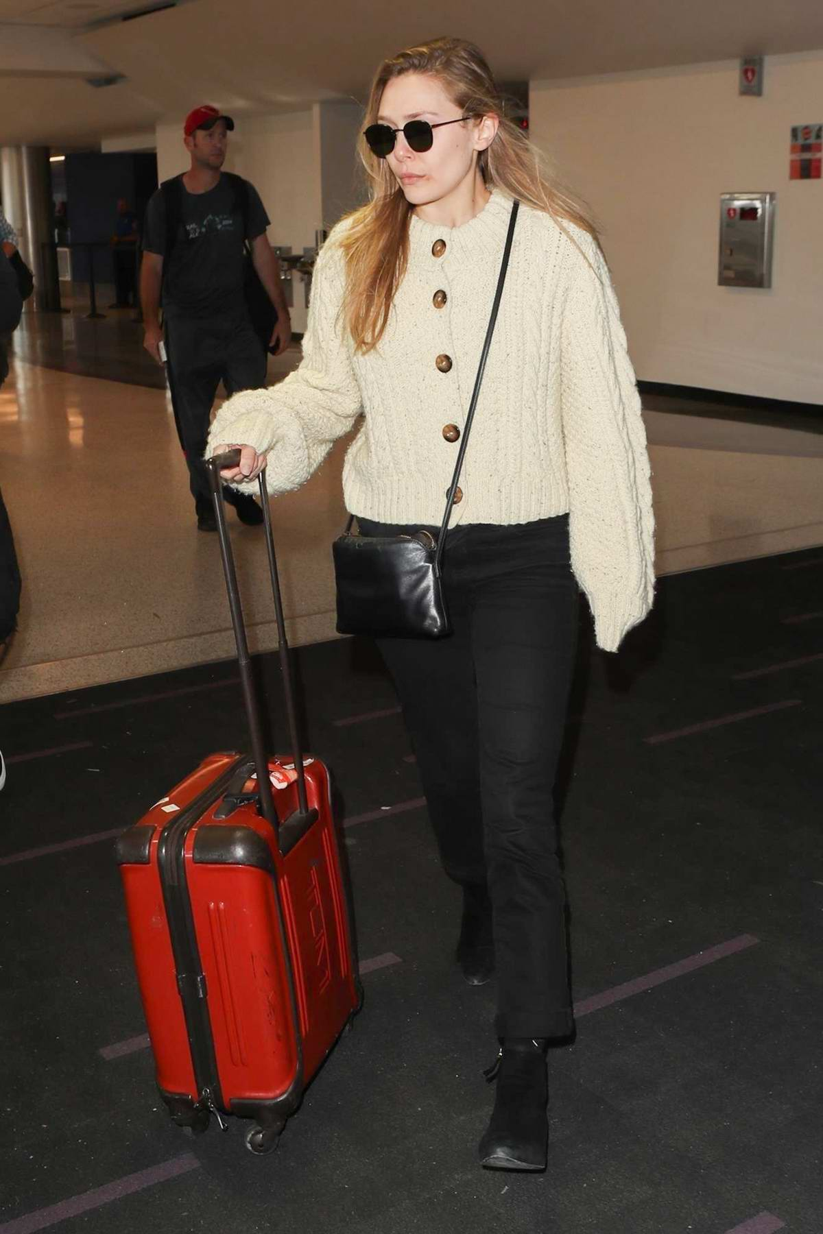 Elizabeth Olsen dressed in a cream sweater and jeans touches down at LAX airport in Los Angeles