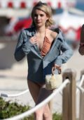 Emma Roberts wears a denim shirt over a swimsuit as she hits the beach with friends in Miami. Florida