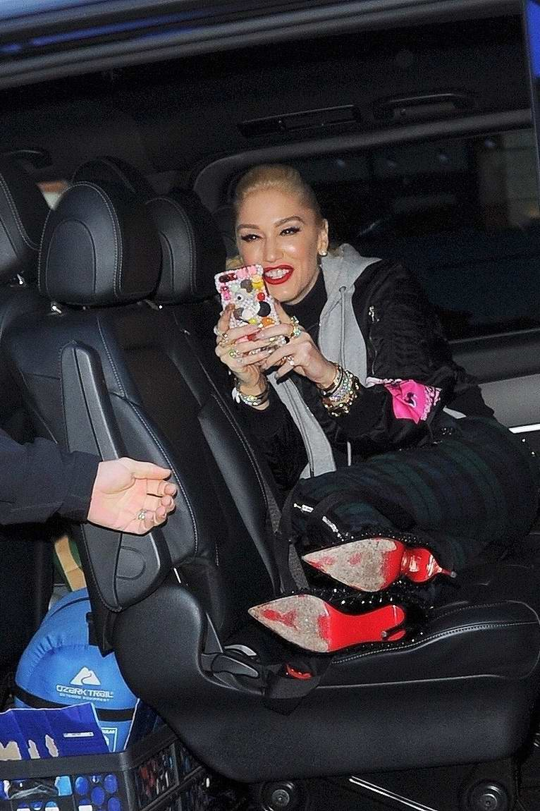 Gwen Stefani turns the tables on the paps taking a sneaky iPhone pic as she arrives at the Global Radio Studios in London