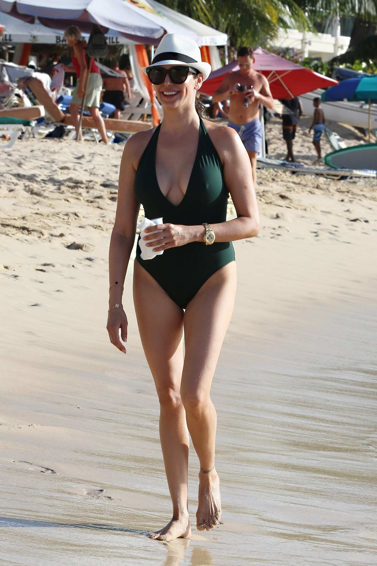 Lauren Silverman wears a green swimsuit at the beach while on holiday in Barbados