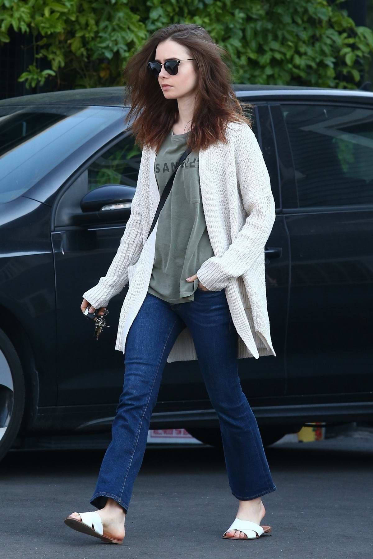 Lily Collins wearing jeans and cardigan over a green t-shirt while running some errands in Hollywood, Los Angeles