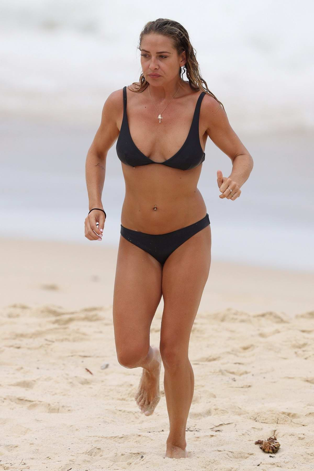 Lisa Clark in a black bikini enjoying the ocean with her boyfriend in Sydney