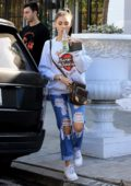 Madison Beer wearing a Harley Davidson sweatshirt and ripped jeans, enjoys a soda while out with a friend in West Hollywood