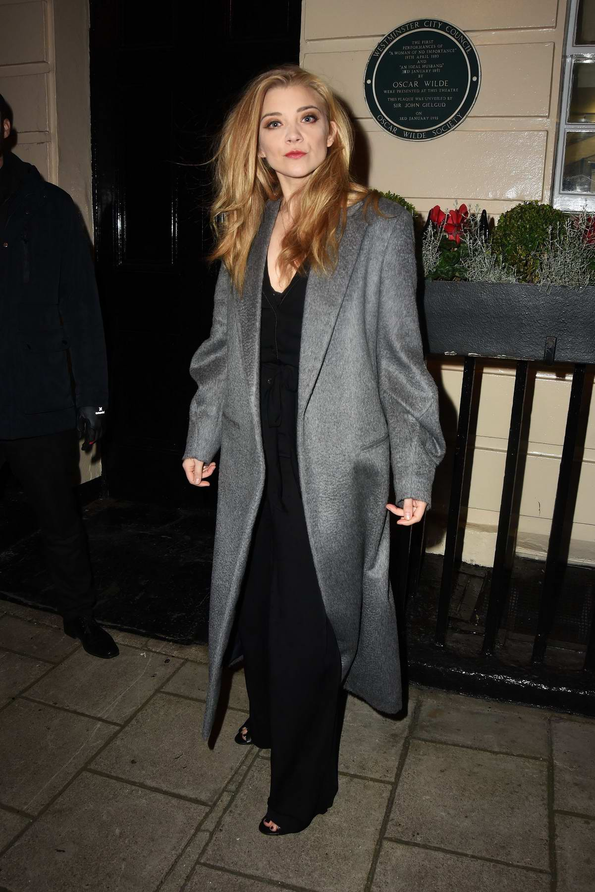 Natalie Dormer dressed in a black jumpsuit with a grey coat while out in London
