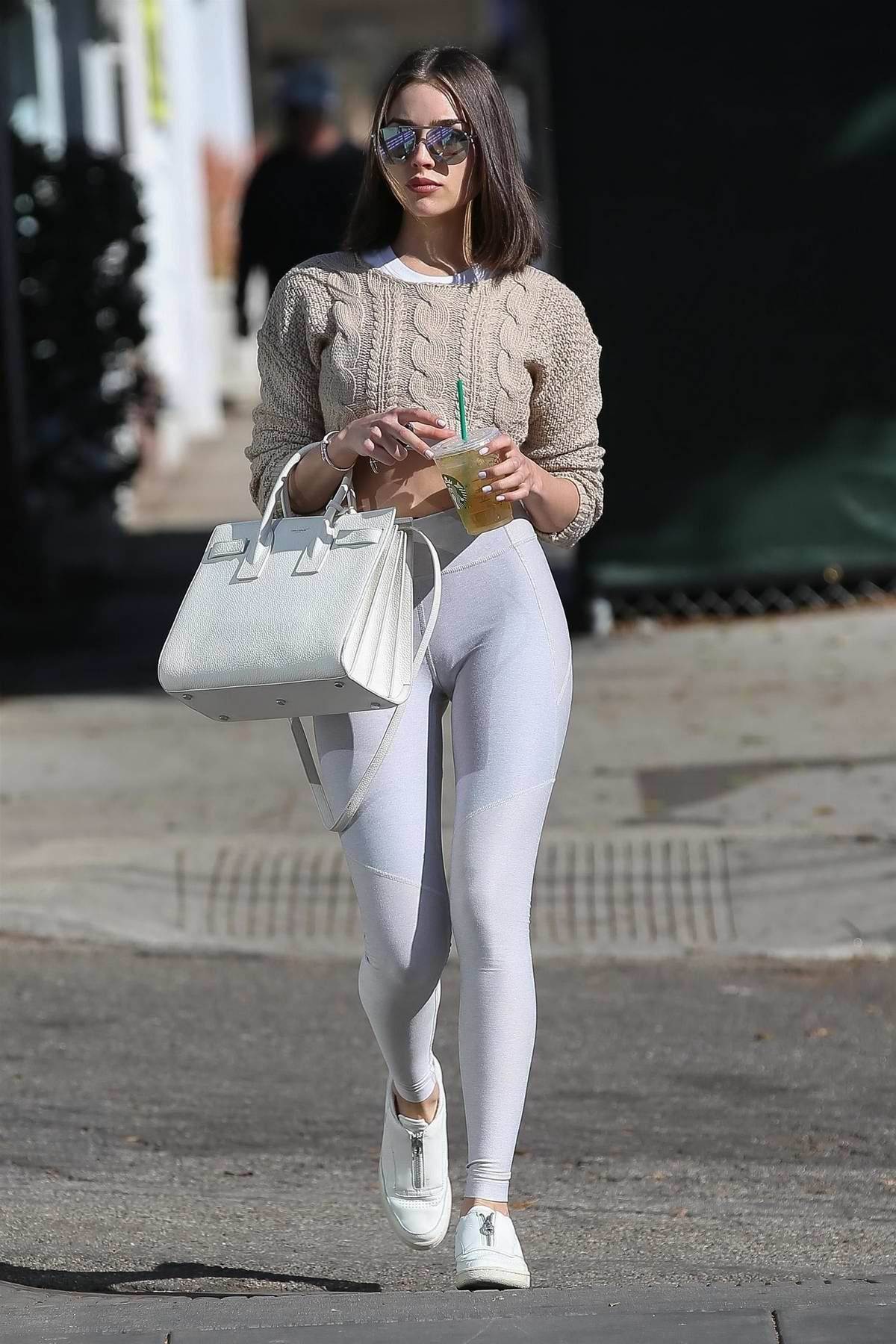 Olivia Culpo wore a cropped knit beige sweater paired with white leggings while she stops by a spa in Santa Monica, California