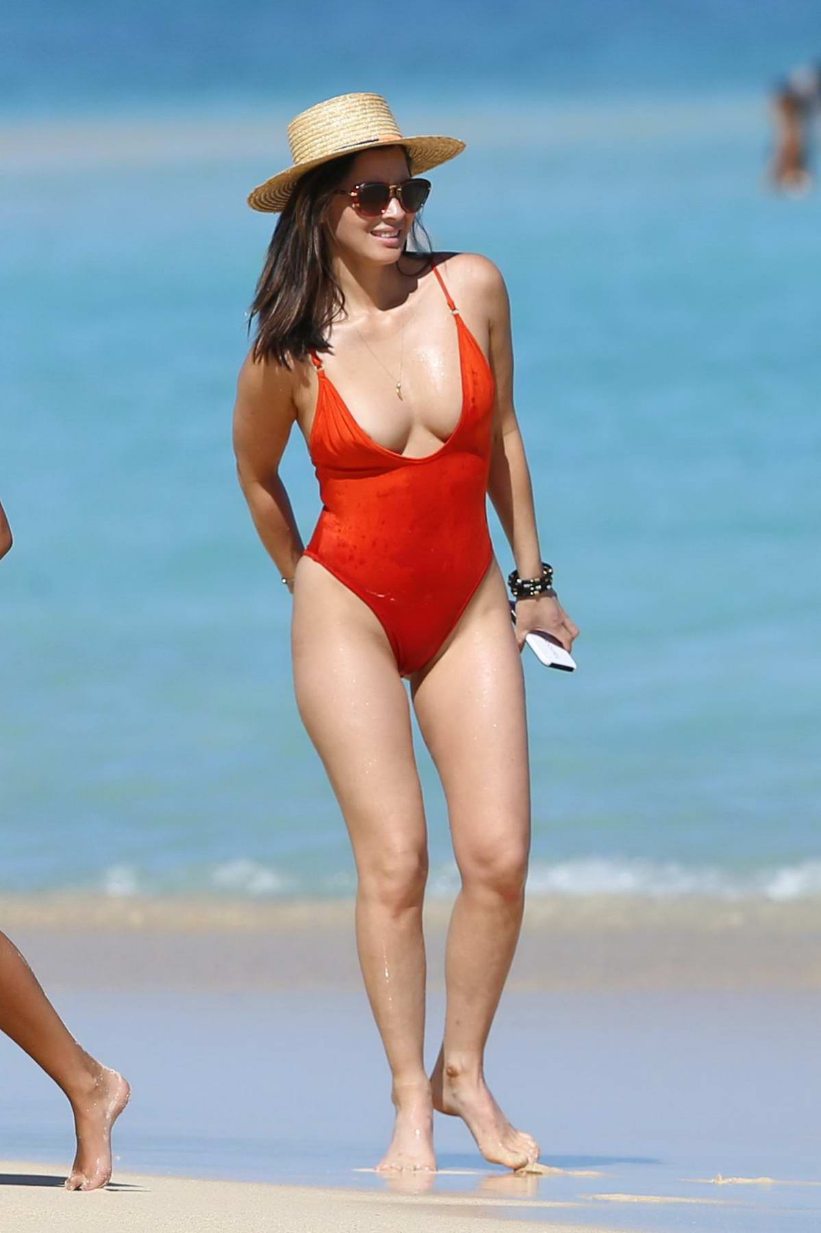 Olivia Munn wears a red swimsuit while she enjoys the day at the beach with friends in Hawaii