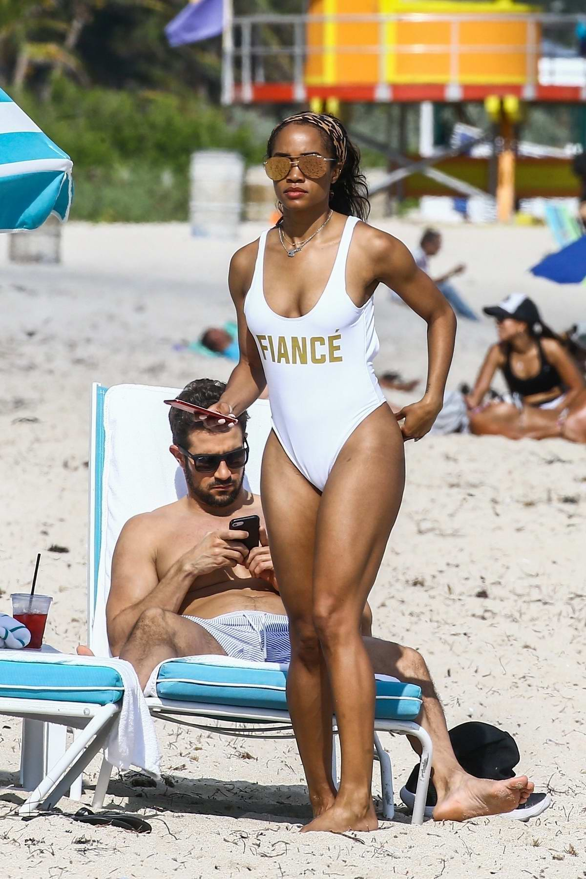 Rachel Lindsay wears a white swimsuit as she hits the beach with finance Brian Abosolo in Miami, Florida