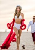 Rachel McCord wears a white bikini with a Santa hat for a Christmas themed photoshoot in Santa Monica, California