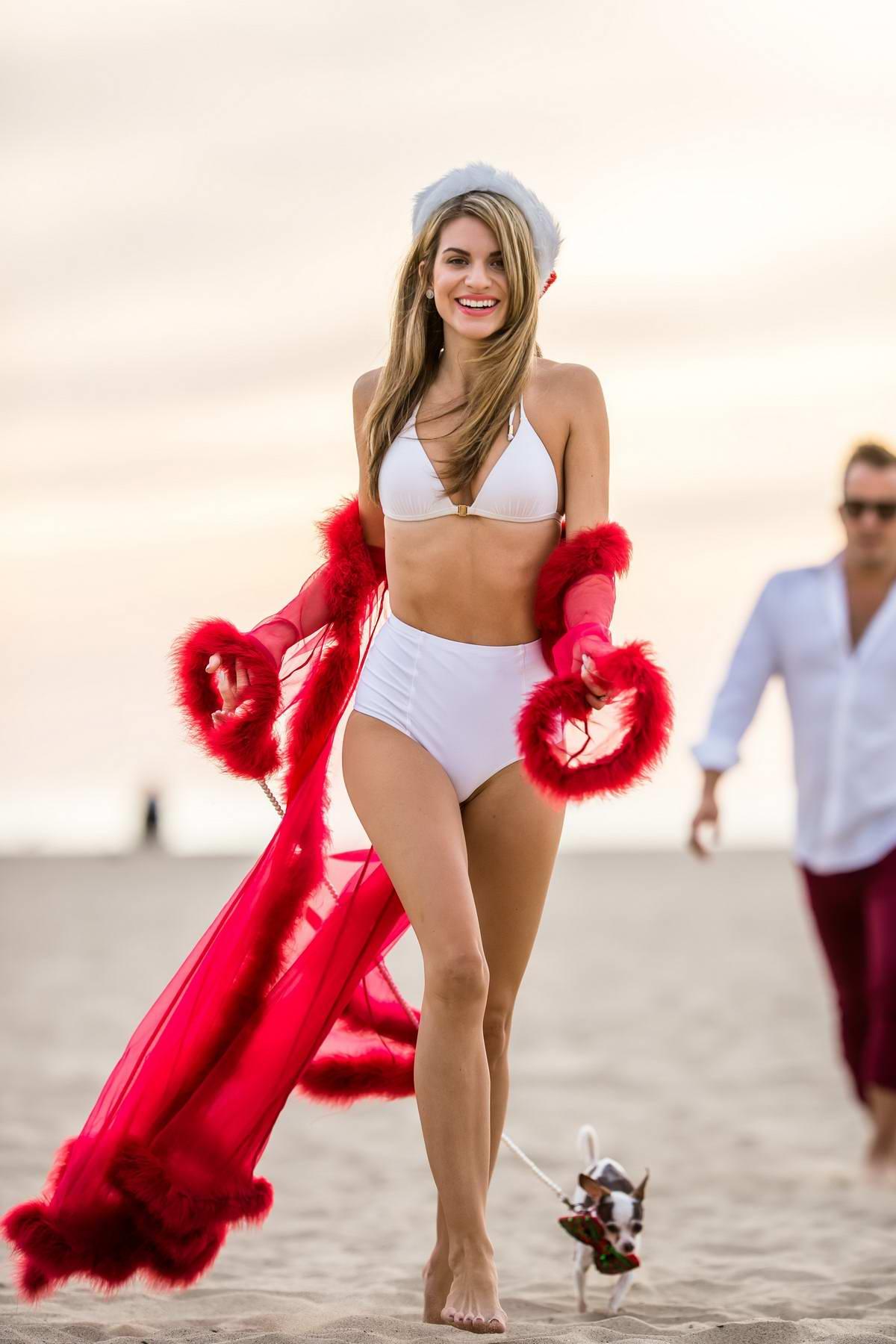 Rachel McCord wears a white bikini with a Santa hat for a Christmas themed photoshoot in Santa Monica, California