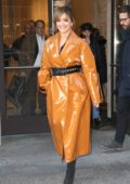 Rita Ora wearing a bright orange vinyl overcoat as she leaves BuzzFeed office in New York City