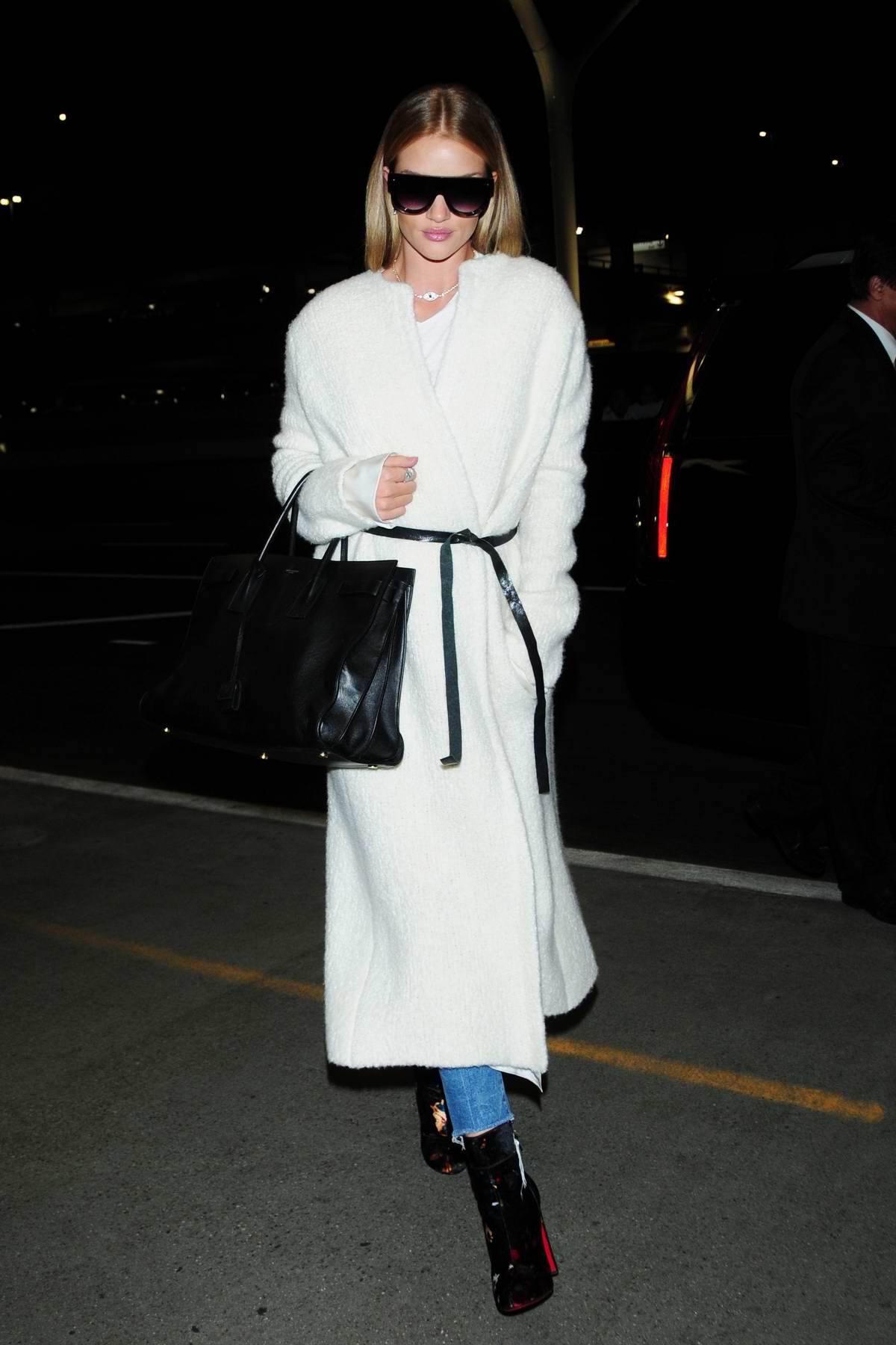 Rosie Huntington-Whiteley dressed in a white robe coat arrives at LAX airport for a flight out of Los Angeles