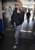 Stella Maxwell keeps it casual in a black personalized jacket and grey sweatpants as she arrives at LAX airport, Los Angeles