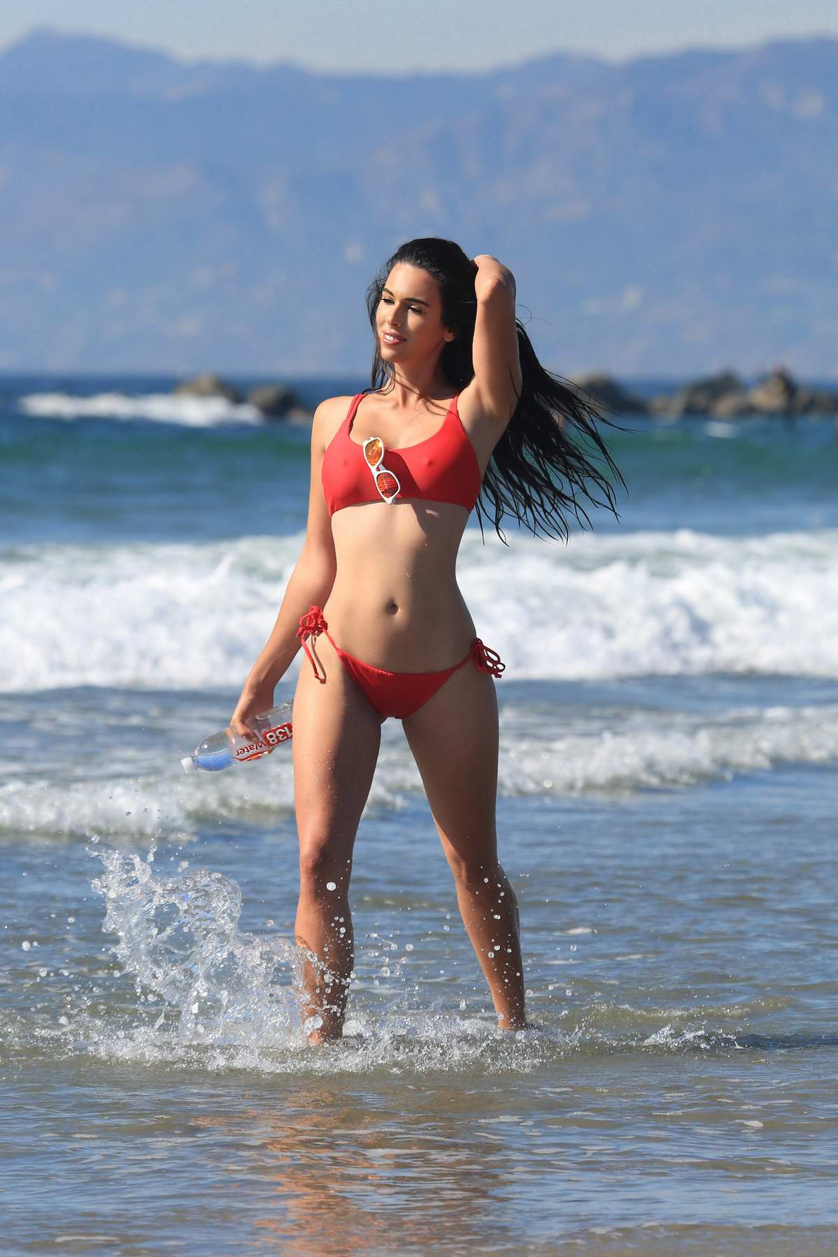 Tania Marie wearing a red bikini as she hits the beach during a 138 Water photoshoot in Venice beach, Los Angeles
