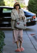 Vanessa Hudgens running errands wearing a cream faux fur jacket and a striped tea dress, Los Angeles