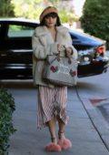 Vanessa Hudgens running errands wearing a cream faux fur jacket and a striped tea dress, Los Angeles
