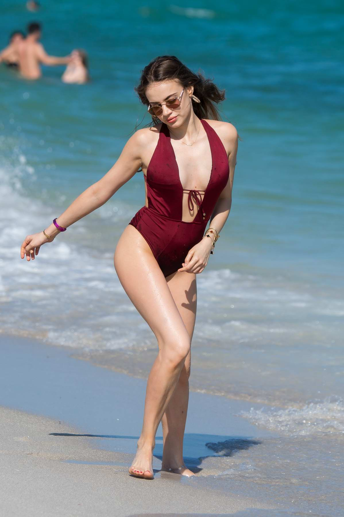 Xenia Tchoumitcheva in a red swimsuit enjoys a day on the beach in Miami, Florida
