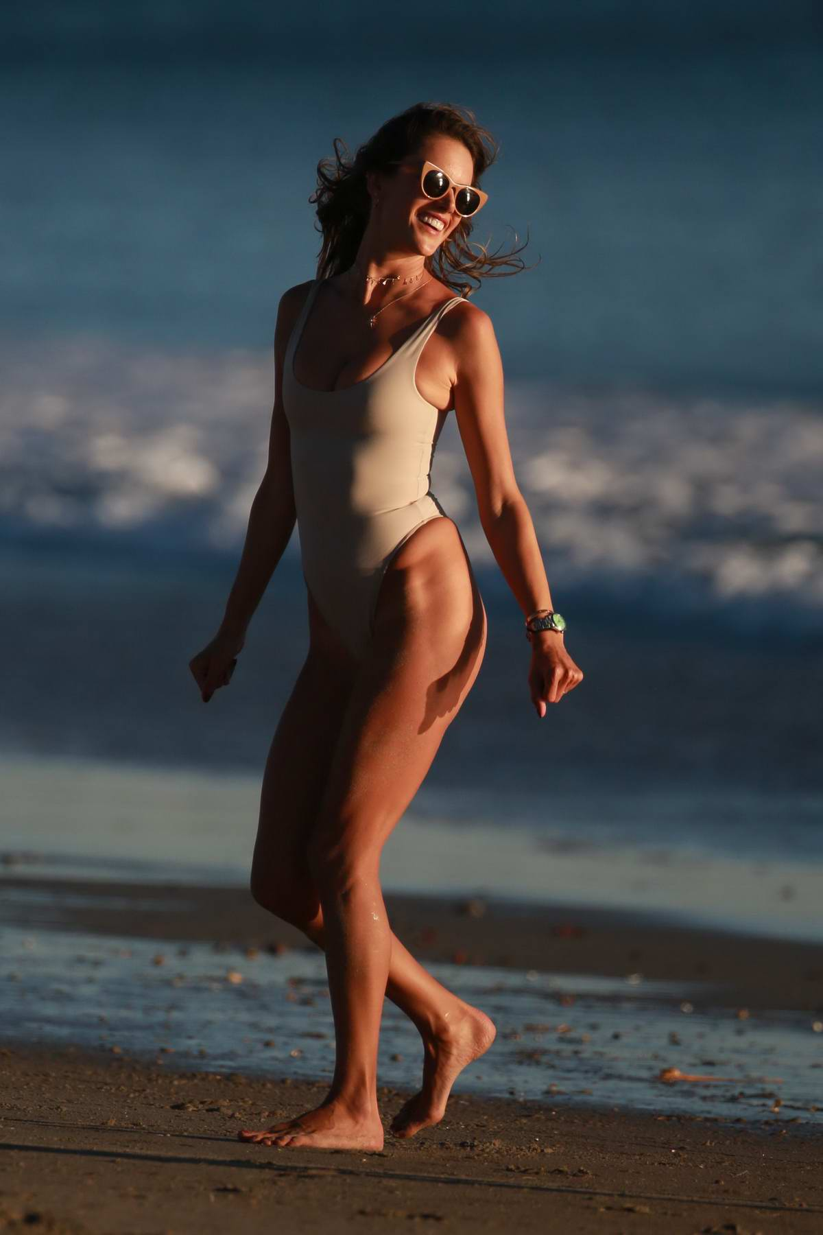 Alessandra Ambrosio in a beige swimsuit enjoys an evening at the beach in Malibu, California