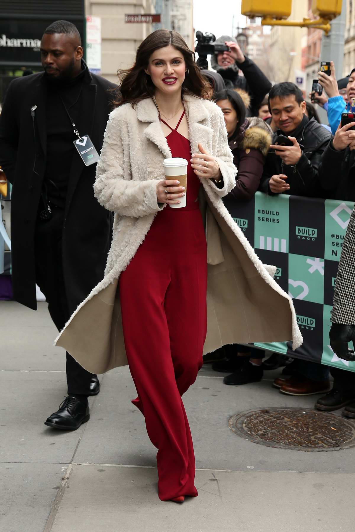 Alexandra Daddario wore a red jumpsuit with a white sherpa overcoat while leaving AOL Build Series in New York City