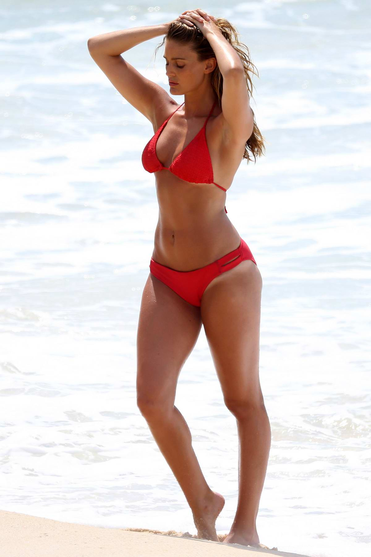 Alyce Crawford poses in a red bikini during a photoshoot at the Bondi beach, Sydney, Australia