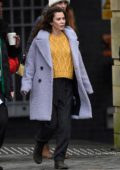 Anna Friel wears a purple coat over yellow sweater while filming scenes in Manchester City Centre in Manchester, UK