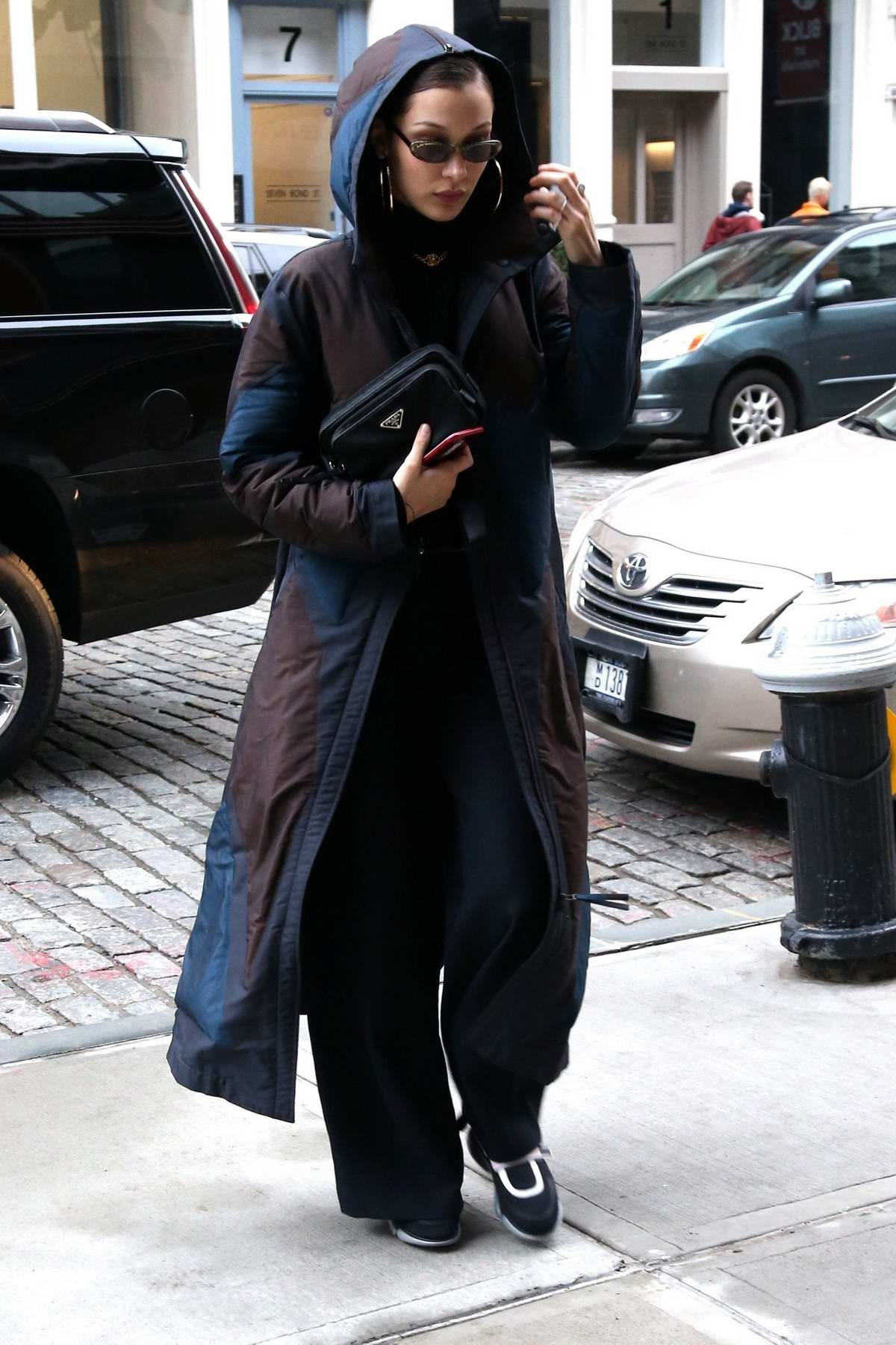 Bella Hadid out wearing a hooded trench coat in New York City