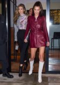 Bella Hadid rocks a burgundy trench coat paired with white boots as she heads out with sister Gigi in New York City