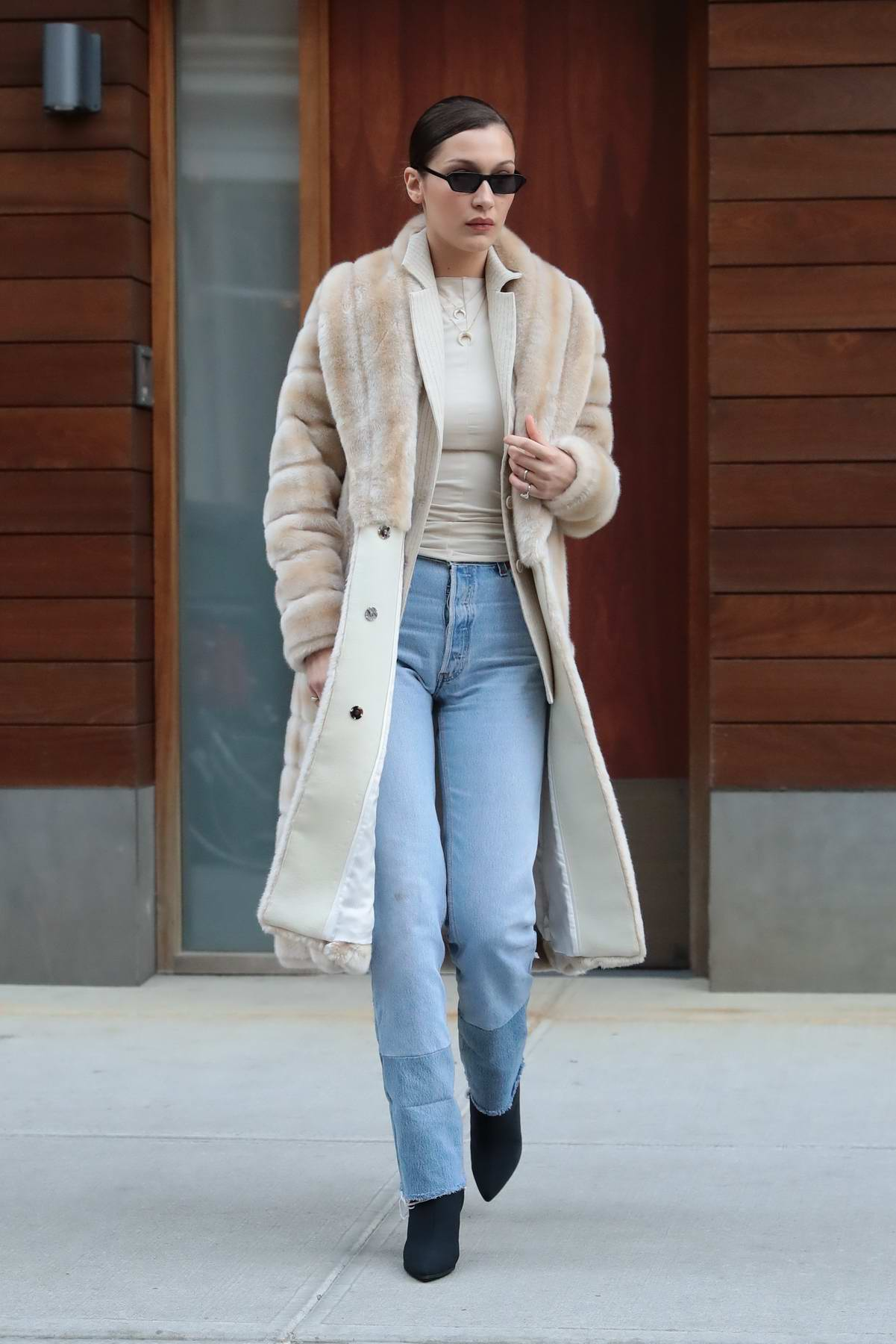 Bella Hadid stays warm under a large fur coat while enjoying lunch with friends at Bar Pitti in New York City