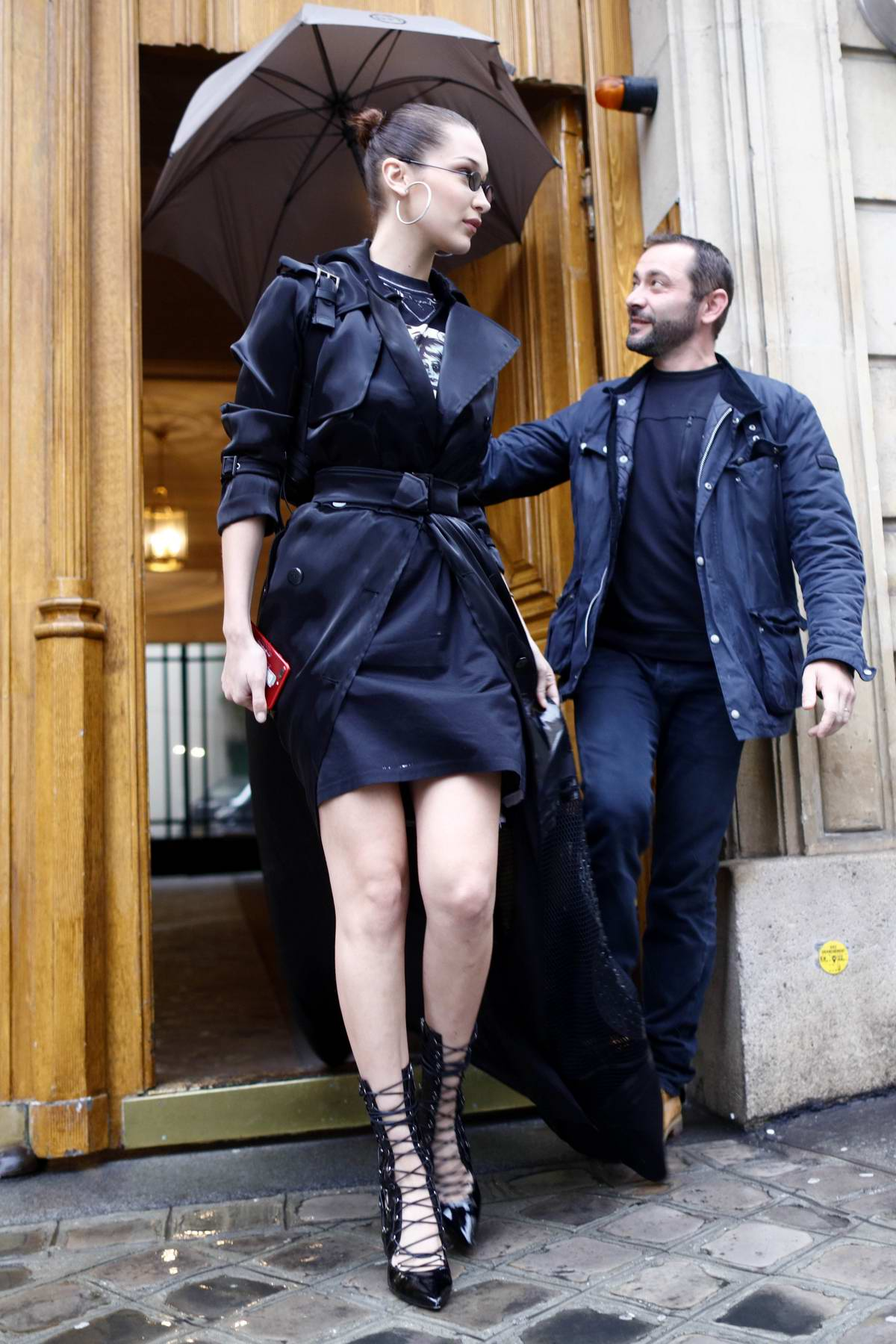 Bella Hadid steps out in a dark blue drape trench coat in Paris, France